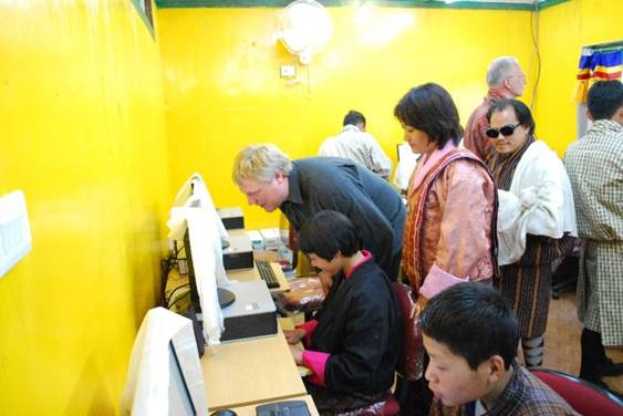 photo: Computer centre opening, Morten. Tshering and Kuenga helping pupils use the computers.