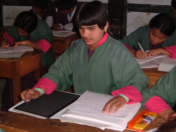photo: Blind pupil in class at school, reading Braille.