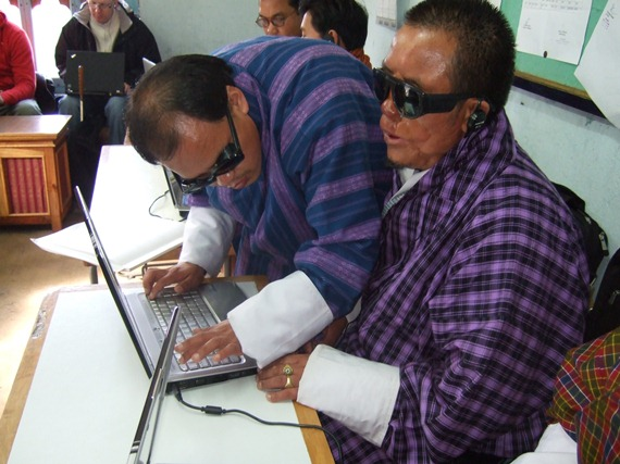 Photo: Kuenga Chhoegyel helping a blind student during ICT training at NIVI.